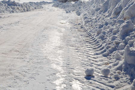 Winter track of snow from the passage of a tractor. The snow glistens from the sunlight. High quality photo
