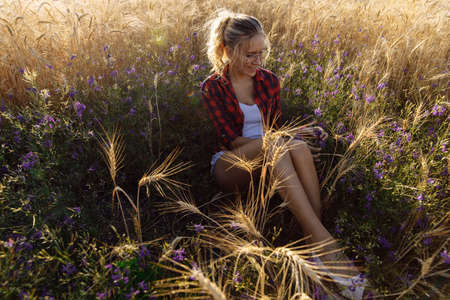 A young woman at sunset sits in a field with flowers and wheat. The flowers are wild purple. The blonde is wearing simple clothes. The woman has a beautiful, even tan. High quality photo