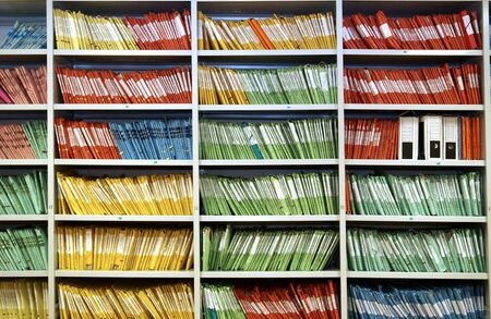 Multicolored folders in a shelf Stock Photo