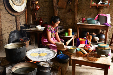 Zinacantan; Estados Unidos Mexicanos - 15 de mayo de 2018: una mujer está cocinando tortillas en una cocina india