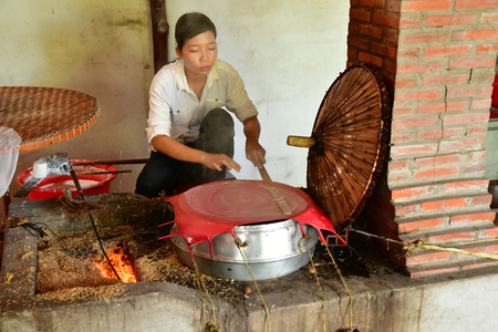 Vinh Long, Socialist Republic of Vietnam - august 17 2018 : a young woman is cooking rice cake Editorial