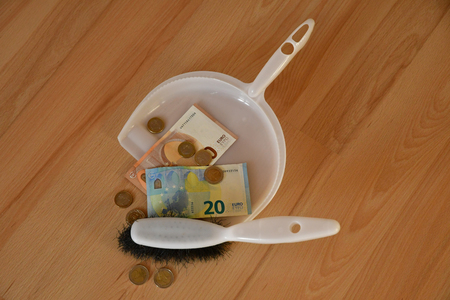 bank notes and coins in a dustpan and a small brush