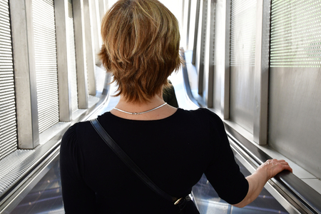Paris La Defense; France - may 25 2017 : a woman in an escalator in La Defense district, the biggest business distric in Europe Éditoriale