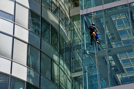 Paris La Defense; France - may 25 2017 : a man is cleaning windows in La Defense district, the biggest business distric in Europe