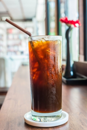 Iced black coffee on the wooden table in coffee cafe. Imagens