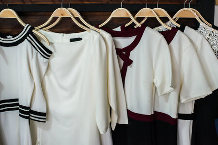 blouses: Many white blouses on hangers in the dressing room.