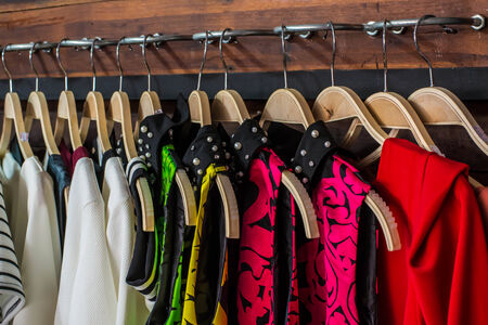 blouses: Many blouses on hangers in the dressing room