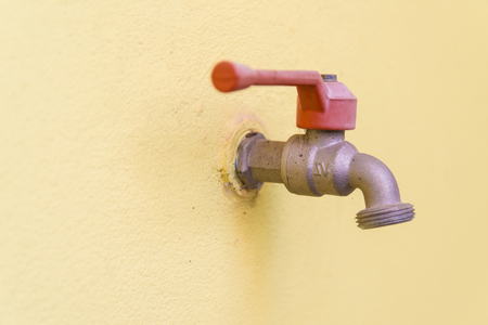 water flowing: Red faucet on a yellow wall background. Stock Photo