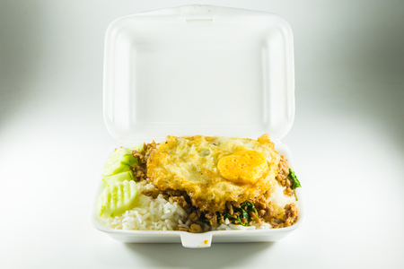 foam box: Rice topped with stir-fried pork and basil in a foam box Stock Photo