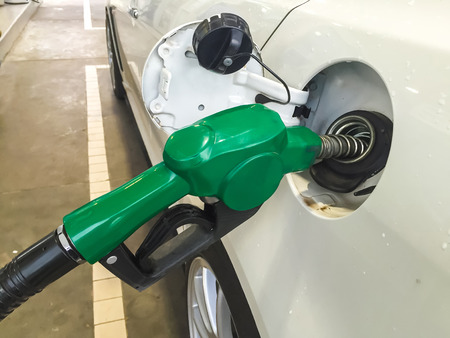 Fuel pump nozzle in the fuel tank of a white car, refuel Stock Photo