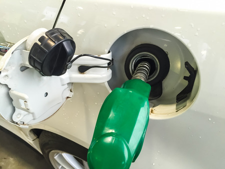 fueling pump: Fuel pump nozzle in the fuel tank of a white car, refuel Stock Photo