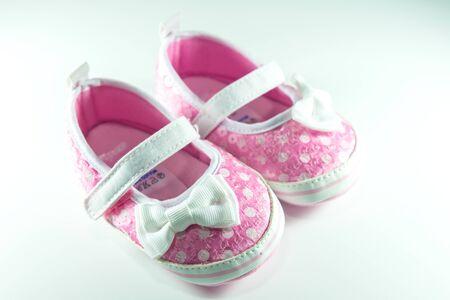 Roze en witte kinderen schoenen op een witte achtergrond.
