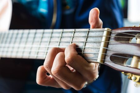 A man playing the classic wooden guitar. Stock Photo