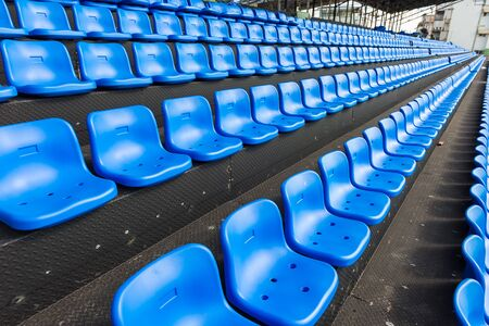 Blue seats on the grandstand of the football stadium. Stock Photo