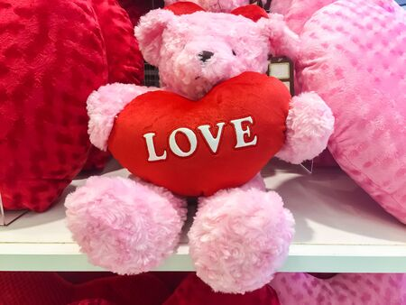 Pink bear doll and red heart. Stock Photo