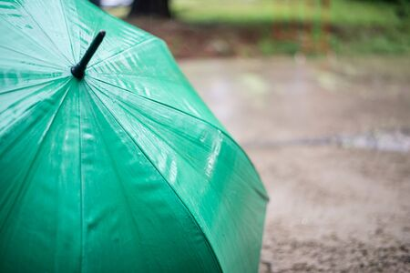Green umbrella placed in the rain.