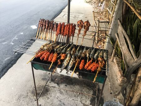 Chicken and fish grilled on a metal grill with smoke.Thailand country food.