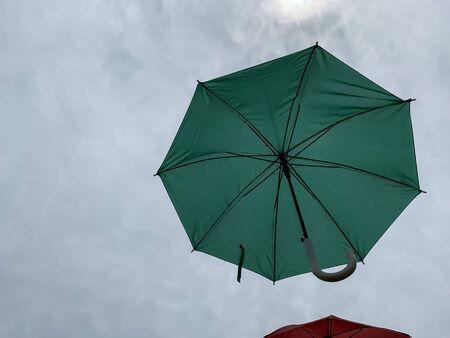 Green umbrella on a cloudy sky. rainy Banco de Imagens