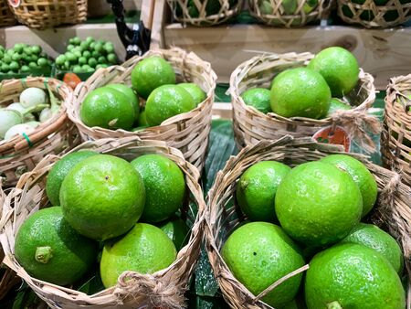 Many limes in small wooden basketry. Thai vegetables Banco de Imagens - 131996578