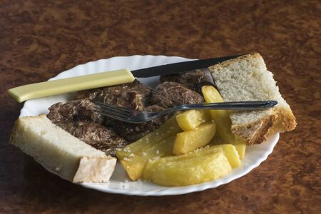 Typical tapas in an Andalusian bar with pig cakes with potatoes and bread natural lighting Stockfoto