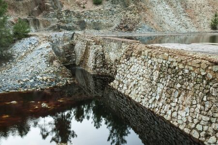 Old abandoned iron mine infrastructure water containment dams with natural light ore