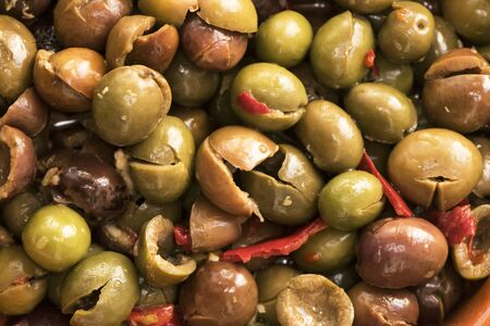 Homemade split and boneless olives, homemade, dressed in the traditional style of southern Cordoba with garlic, dried red peppers, oregano, salt and vinegar lighting by flash