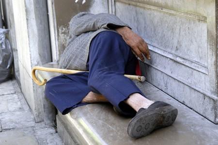 Beggar sleeping on a bench Stock Photo