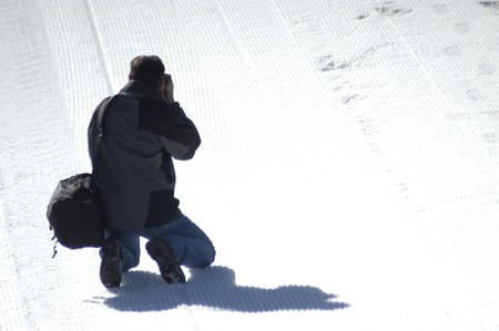 Photographer making photographs on the icy snow in Sierra Nevada