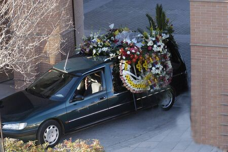 coffins: Hearse with wreaths of flowers