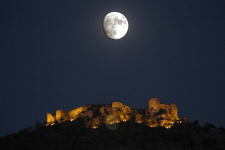 Old fortress of the Arab town of Pinar, in the province of Granada, with the people below, illuminated photo