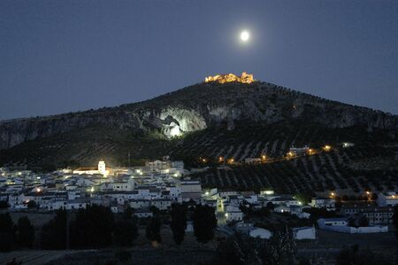 reconstructing: Old fortress of the Arab town of Pinar, in the province of Granada, with the people below, illuminated