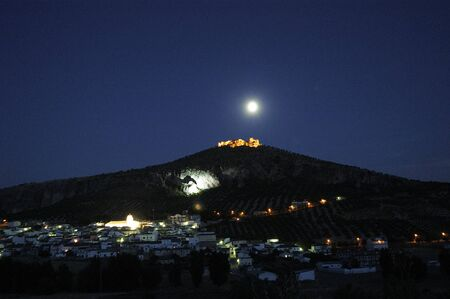 pinar: Old fortress of the Arab town of Pinar, in the province of Granada, with the people below, illuminated