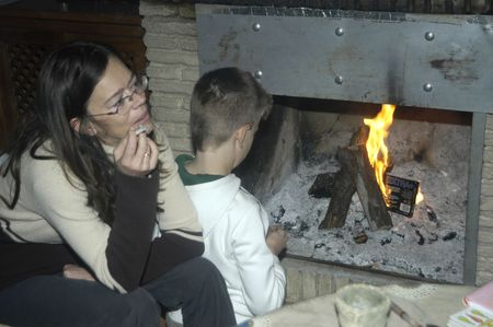 between 5 and 10 years: Mother smoking with his son, beside the fireplace