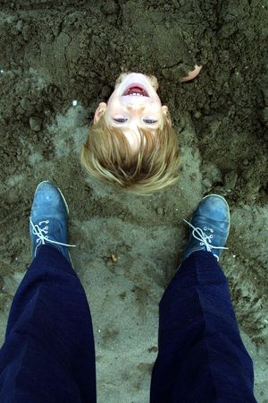 head in the sand: Boy buried in sand with his head out