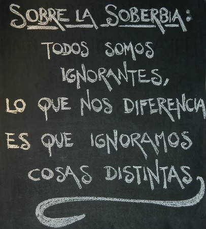 phrases: Chinese proverb about the arrogance and ignorance written in chalk on a blackboard in Spanish