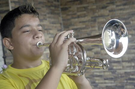 teenage boy playing the trumpet photo