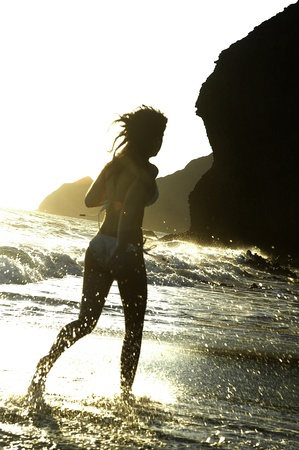 young woman running on the beach photo
