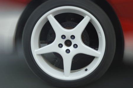 wheel of a car accelerating with blurred background photo