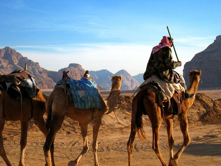 Beduinen auf Kamelen in der Wüste Wadi Rum, Jordanien
