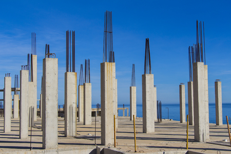 concrete and iron pillars, pouring of concrete against the blue sky, concrete formwork