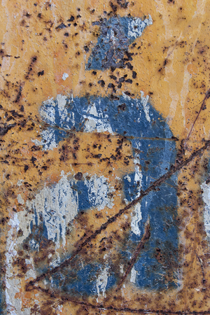 blue letter with tilde scratched rusty metal background, blue stencil painted on rusty background, letter a with tilde