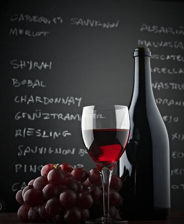 oenology: red wineglass, grapes, a bottle and blackboard. low-angle shot
