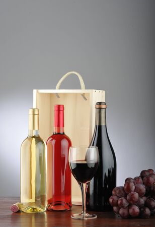 still life of red wine, white, rose, glass of wine, grapes, bottle and cork with wooden box behind photo