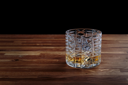 whiskey is poured into a crystal glass with ice standing on the oak surface of the table Stock Photo