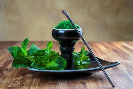 Shisha mint in glossy black cup on a plate with fresh mint leaves