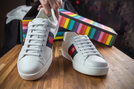New white sneakers on the wooden surface on the background of gift boxes unpacked