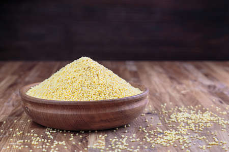 Millet in a wooden bowl standing on the kitchen table made of oak.