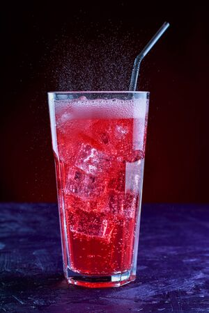 fizzy drink with ice in glass on dark background
