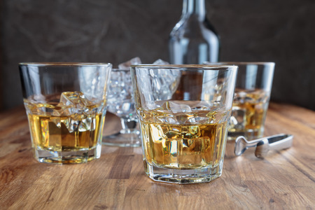 three glasses of whiskey on the oak surface of the table