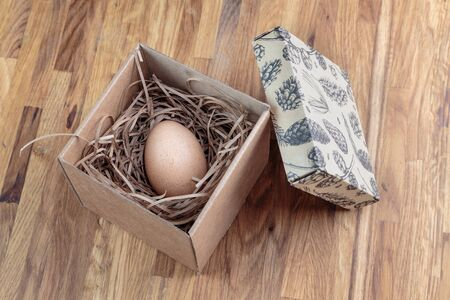 chicken egg in an open cardboard box with a lid, in a soft package